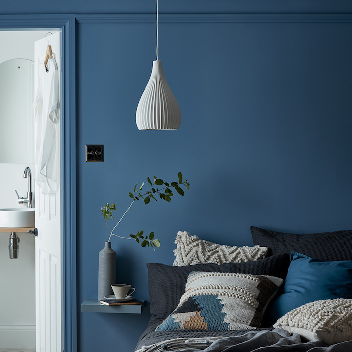 mur pantone bleu couleur interieur, coussins de tons foncés sur un lit avec linge de lit gris, suspension blanche