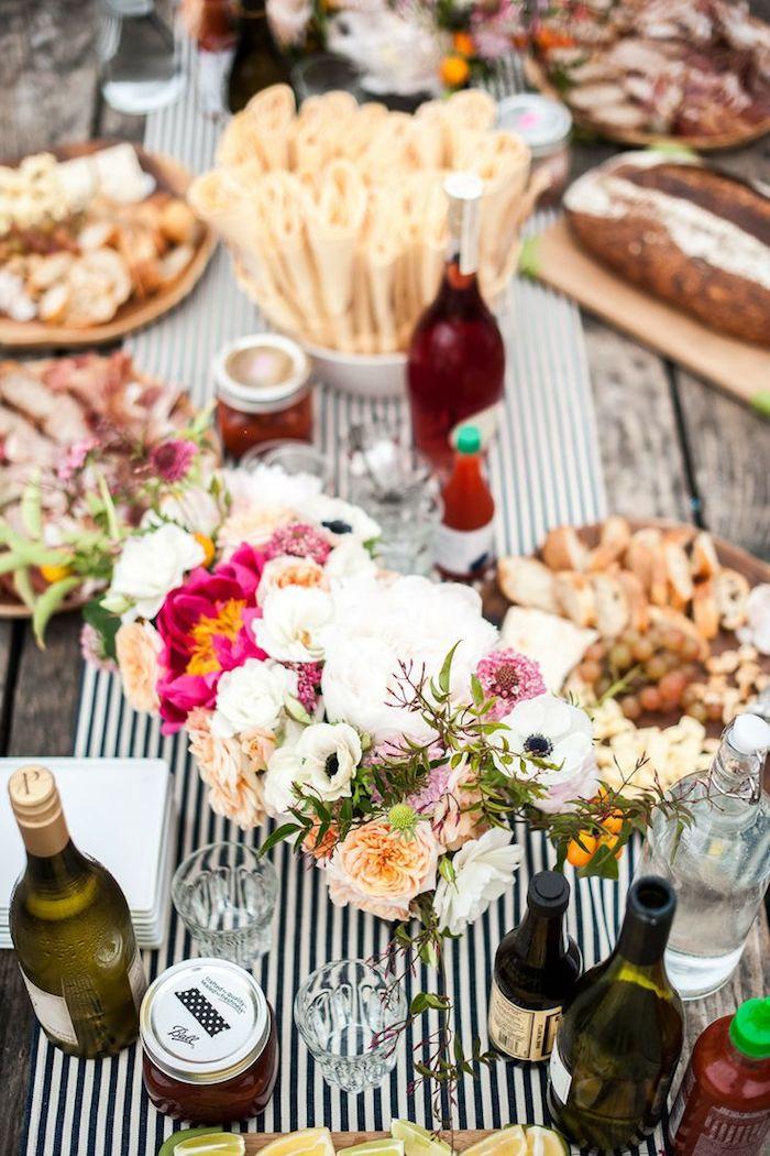centre de table en fleurs colorées sur chemin de table noir et blanc, plusieurs plats za partager entre amis, anniversaire en plein air