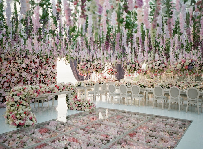 theme mariage floral avec des fleurs suspendues du plafond, guirlande de fleurs et sol avec fleurs sous verrière