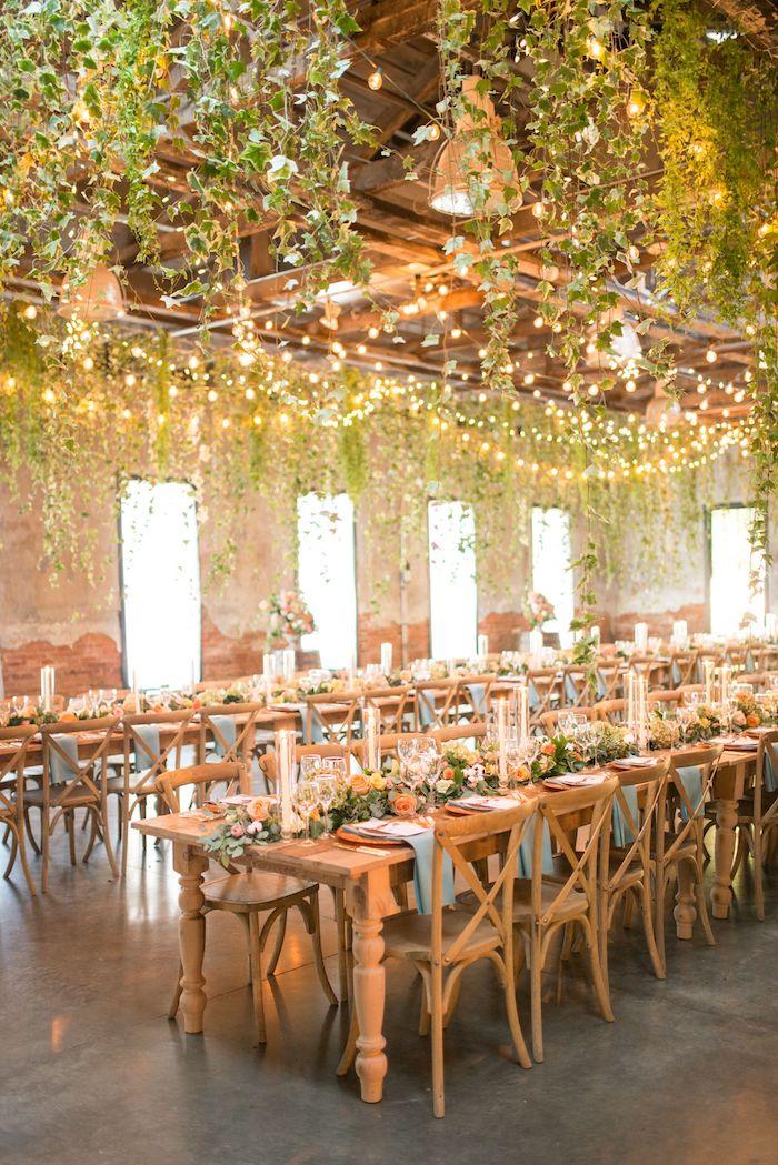 idee deco plafond mariage avec végétation grimpante et guirlandes lumineuses au dessus de chaises et table bois végétalisée, theme de mariage champetre dans vieilles granges