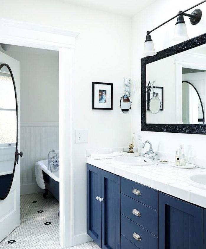 modele salle de bain épurée en blanc et bleu pantone, plan de travail carrelage blanc, miroir avec cadre noir, éclairage miroir, murs blancs