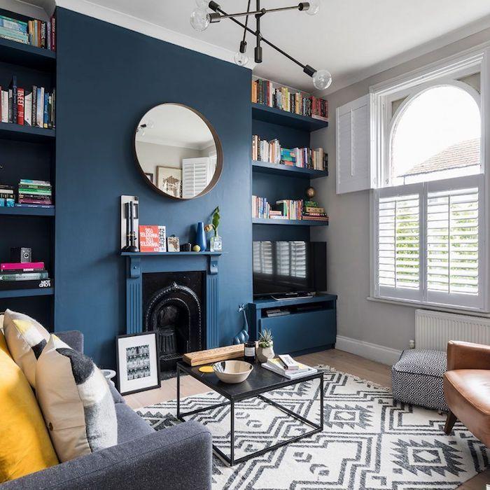 deco salon bleu nuit, tendance couleur 2020, tapis gris et blanc, table basse noire, canapé gris avec coussins jaune et gris, suspension originale