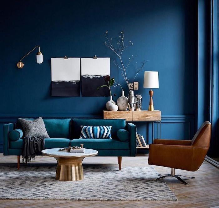 deco salon bleu avec canapé bleu paon et fauteuil en cuir marron, tapis gris et blanc, table en laiton, murs avec art noir et blanc