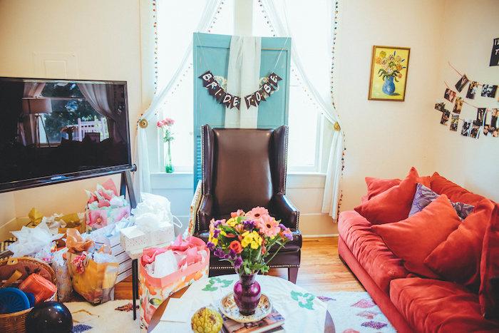 deco de fete theme friends, fauteuil cuir marron, canapé rouge, parquet bois clair, bouquet de fleurs sur table basse