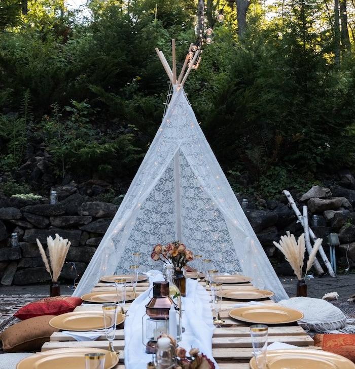 tente indienne dentelle blanche et table basse de bois et des assiettes or, centre de table vole blanche, lanterne