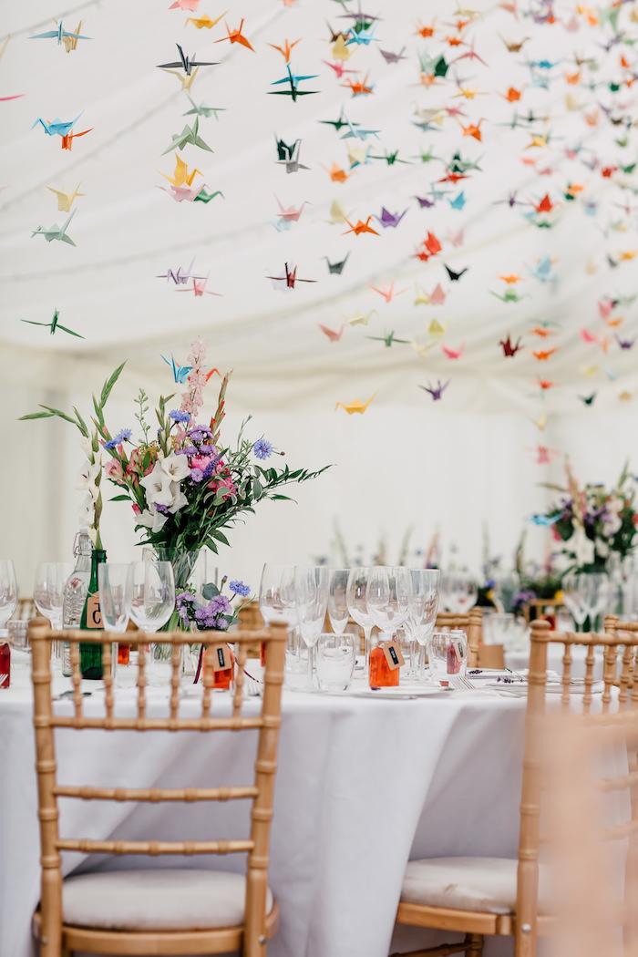 origami papier coloré grues suspendues du plafond et décoration de bouquet de fleurs champetres colorées sur nappes blanches, decoration salle mariage colorée