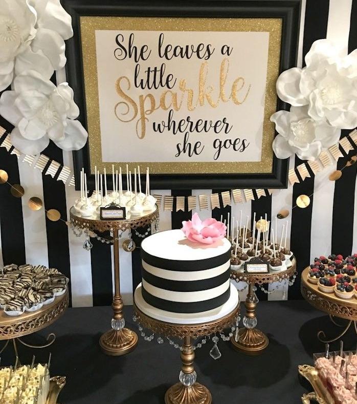 deco de table anniversaire noir, blanc et or, gateau noir et blanc, support gateaux avec peits gateaux sur nappe noire