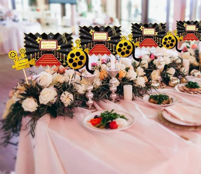 deco de table anniversaire cinémá hollywood, nappe blanche, guirlande de roses blanches, motif cinéma deco