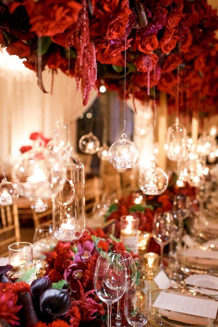 idee decoration mariage, table décorée de fleurs rouges comme centre de table mariage et lumières dans petits terrariums en verre