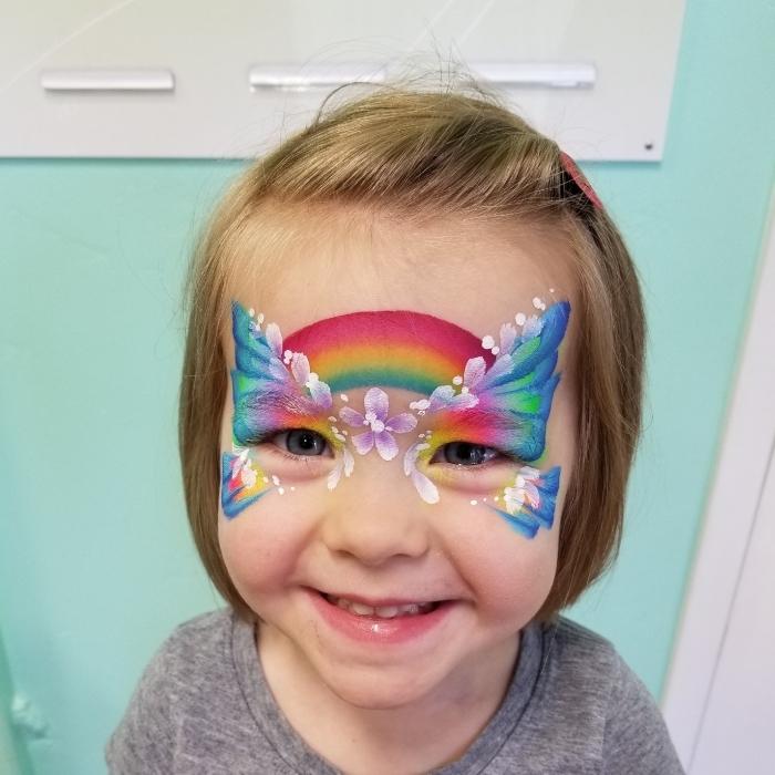 idée de maquillage halloween facile pour enfant à réaliser avec peinture faciale et pochoir à effet papillon et arc en ciel