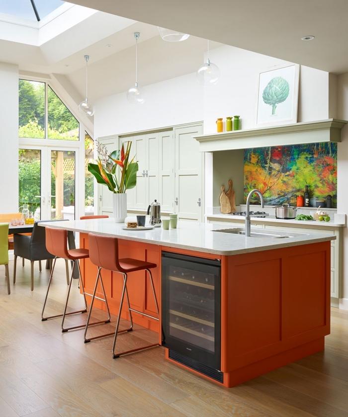 tendance cuisine 2020 aux murs blancs avec façades en vert pastel et un îlot central à design plan de travail blanc et façades orange