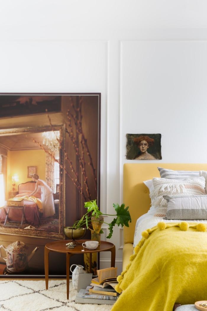 idée déco chambre adulte aux murs blancs et parquet bois clair avec grand lit à tête tissu jaune et éléments de style retro