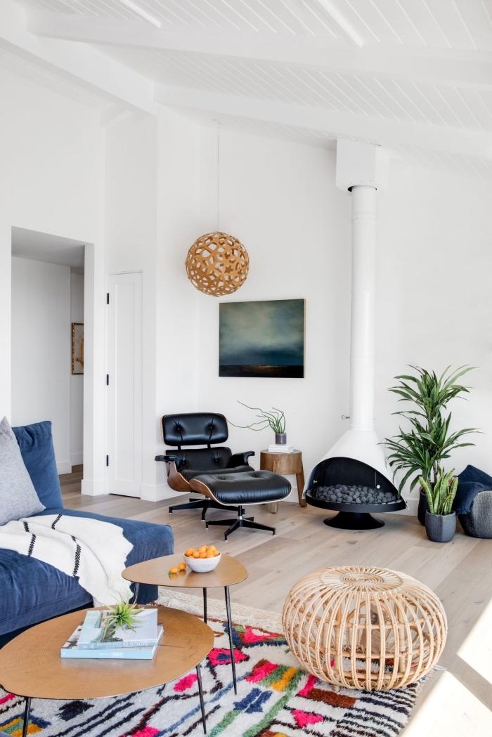 salon blanc au parquet bois clair aménagé avec canapé bleu et table de salon double plateau en bois et fer noirci, deco salon moderne