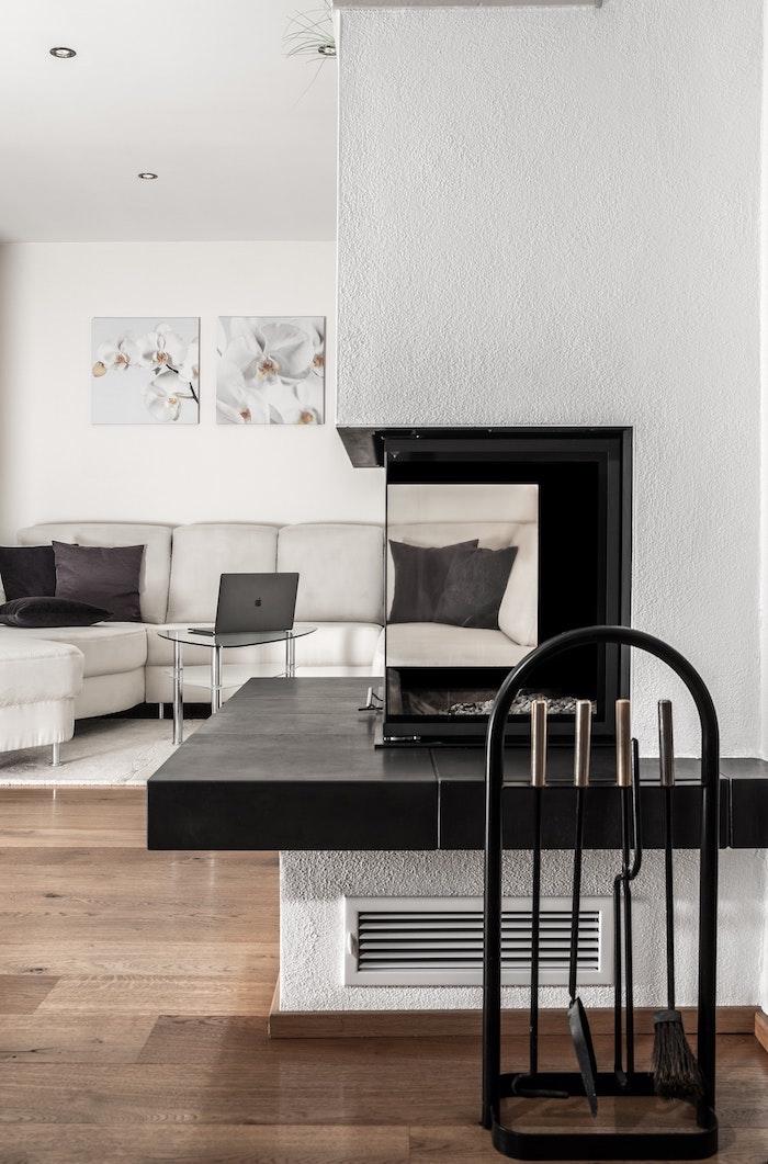 Noir et blanc salle de séjour avec cheminée transparente, idée canapé blanc en angle, table basse en verre