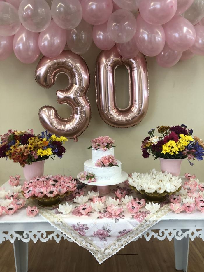 decoration anniversaire adulte en nuances de rose et blanc, table blanche décorée avec gâteau anniversaire et bouquets de fleurs fraîches