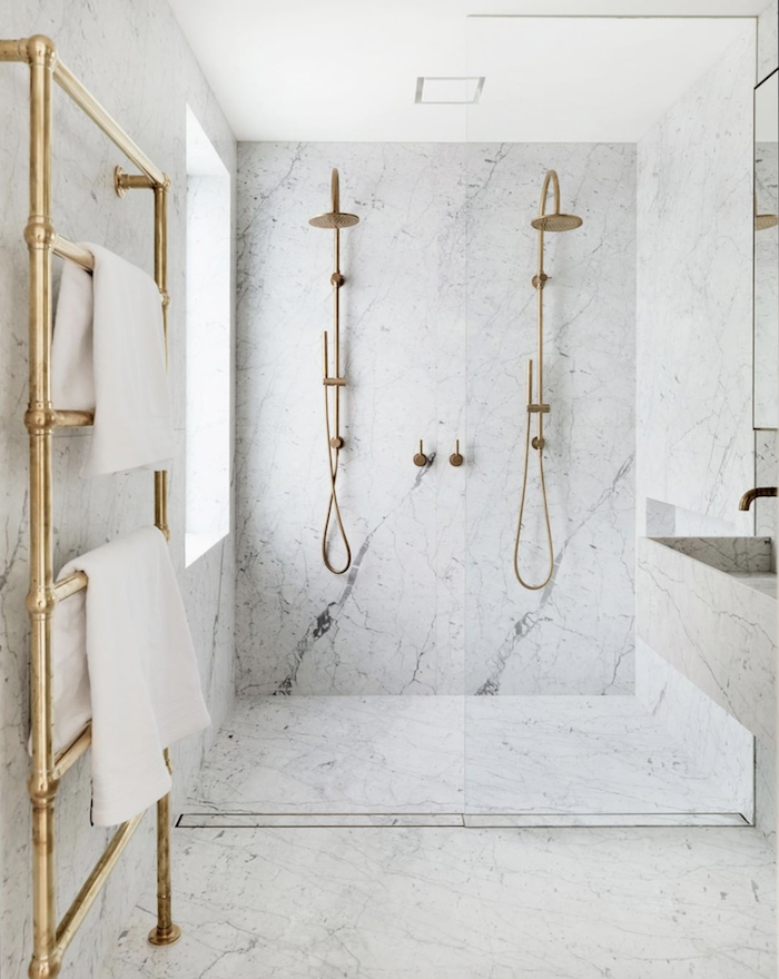 Echelle de rangement doré dans la salle de bains marbre blanc, douche doré double, salle de bain retro avec accents lux, salle de bain en marbre blanc