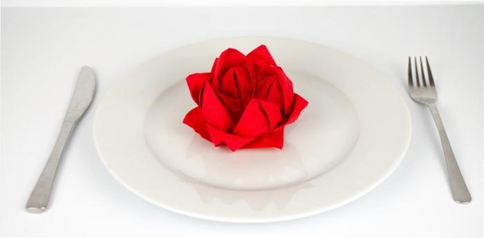 idée de pliage de serviette en papier facile fleur, déco de table romantique avec assiette blanche et serviette rouge
