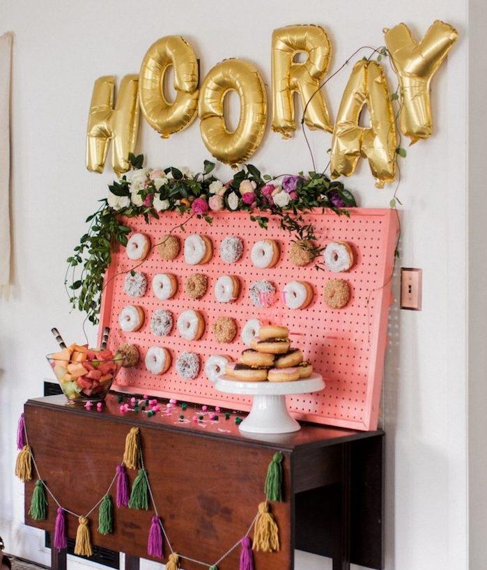 panneau perforé décoré de beignets avec decoration de guirlande de fleurs, ballons en lettres dorées, meuble candy bar bois vintage