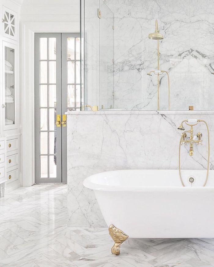 Blanc baignoire ovale à pieds dorés, douche et lavabo or, salle de bain en marbre blanc, beauté dans la simplicité design pure