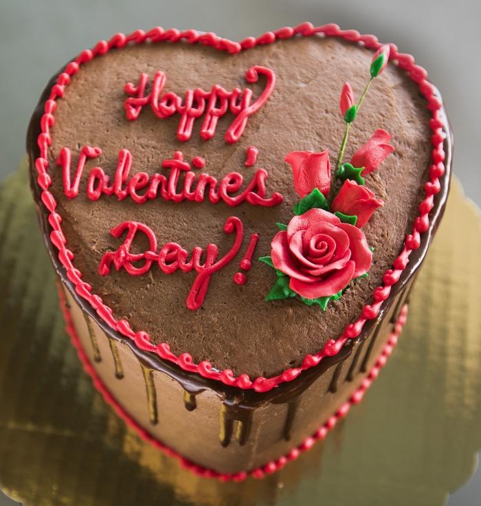 exemple de gateau coeur au caramel et chocolat noir avec décoration Joyeuse Saint Valentin et petits fleurs rouges