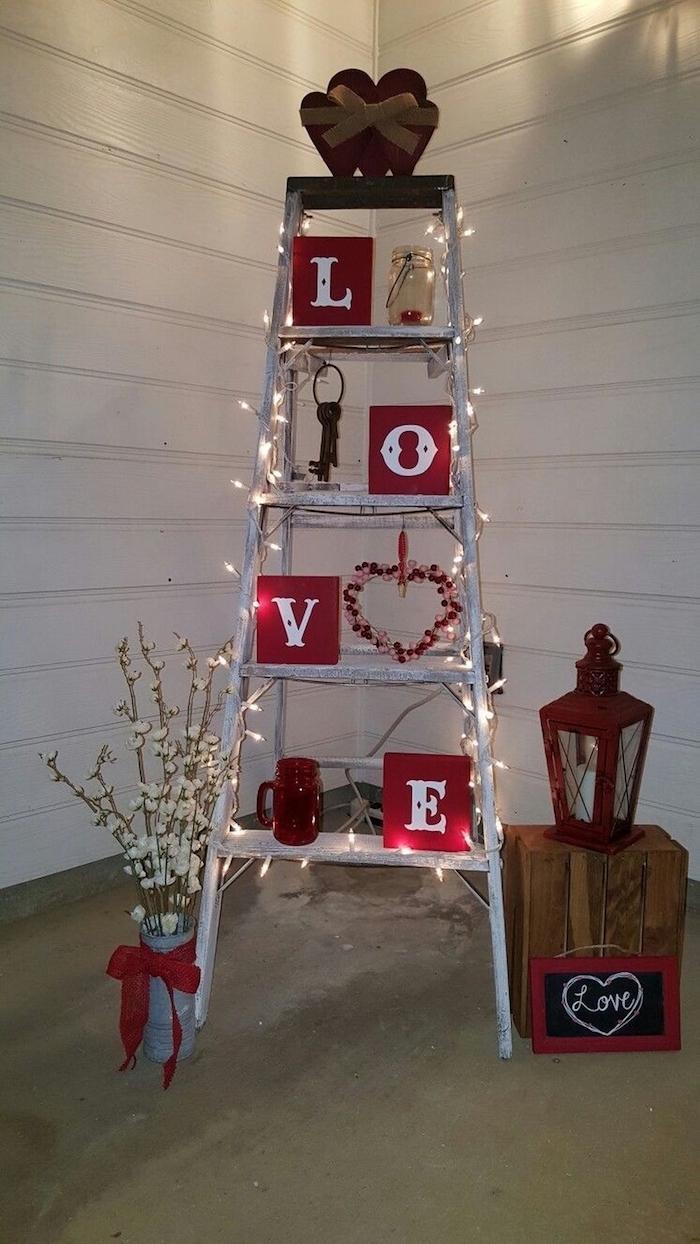Escalier décoré avec guirlande lumineuse, lettres pour écrire amour et boite à la forme de coeur en top, idée saint valentin, inspiration fête déco de table pour la saint valentin