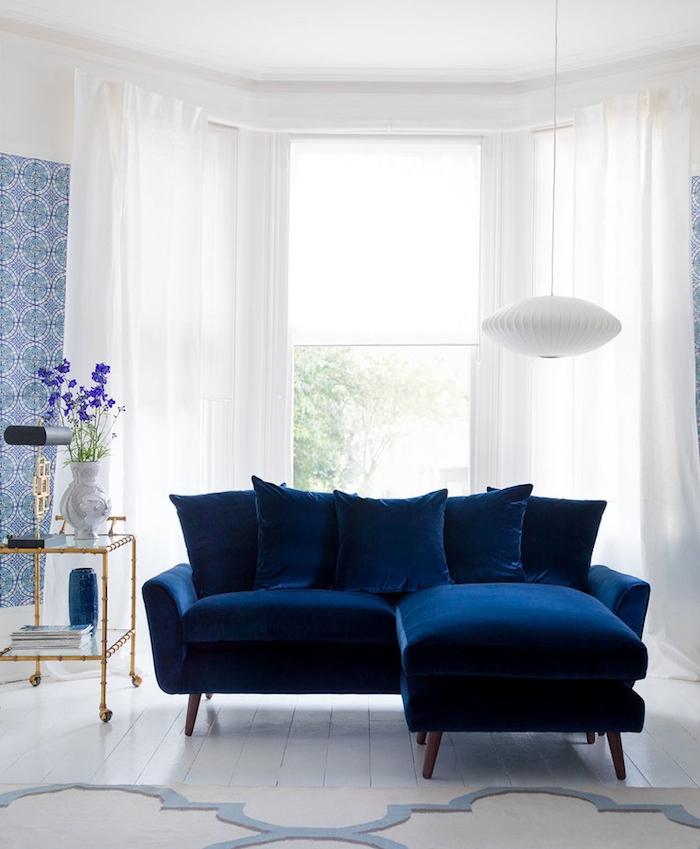 modele de canapé bleu nuit dans un salon blanc avec décoration murale lé de papier peint blanc et bleu imprimé floral