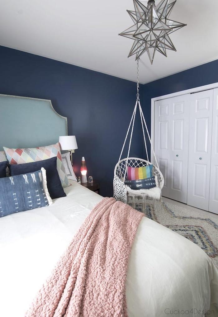 couleur peinture chambre bleu foncé, balançoire suspendu, coussins décoratifs colorés, plaid rose, tapis gris et blanc, suspension étoile