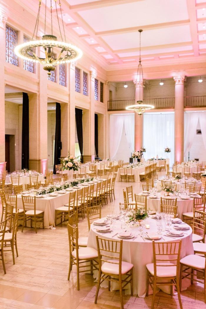 lustres avec lumières au dessus de table en nappe blanche et chaises bois et blanc, murs blancs, parquet salle de mariage clair