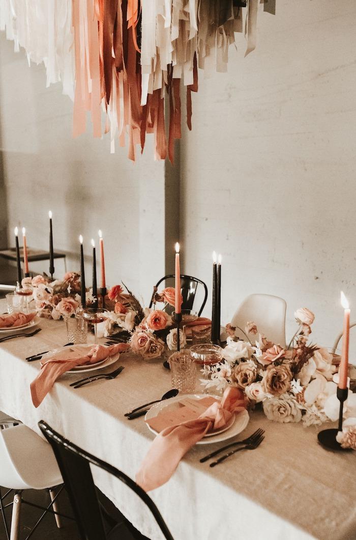 chutes de tissu colorées au dessus d une table décorée de composition florale en fleurs rose et blanches, serviettes roses, chaises noir et blanc industrielles