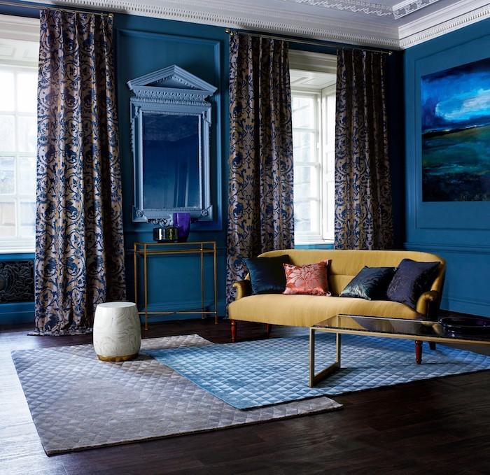 canapé jaune décoré de coussins dans un salon bleu foncé avec tapis gris et tapis bleu sur parquet bois foncé, rideaux gris et bleu