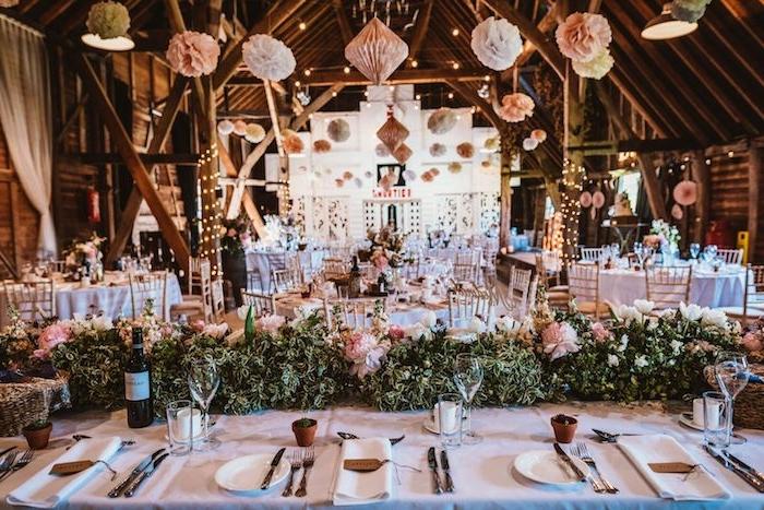 deco plafond mariage en fleurs de papier suspendues, chemin de table feuillages et fleurs rose sur table en nappe blanche, idée thème mariage champetre chic dans granges