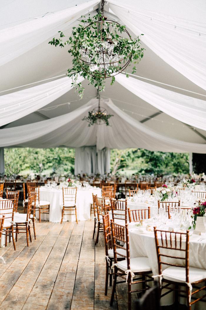 plafond drapé avec voiles blanches tendues, suspension globe végétalisé au dessus de tables décorées de nappes blanches avec chaises blanc et bois, parquet bois brut