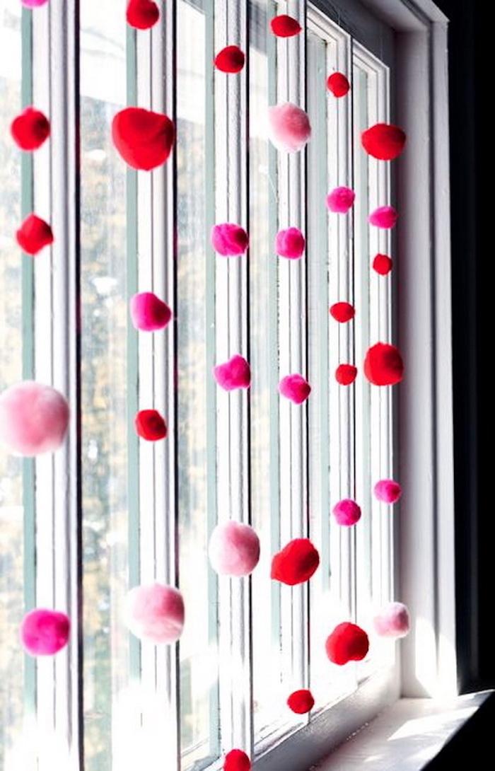Pompons déco rose et rouge, idée fenêtre déco simple avec guirlandes de pompon, idee saint valentin, romantique idée de surprise pour la fête