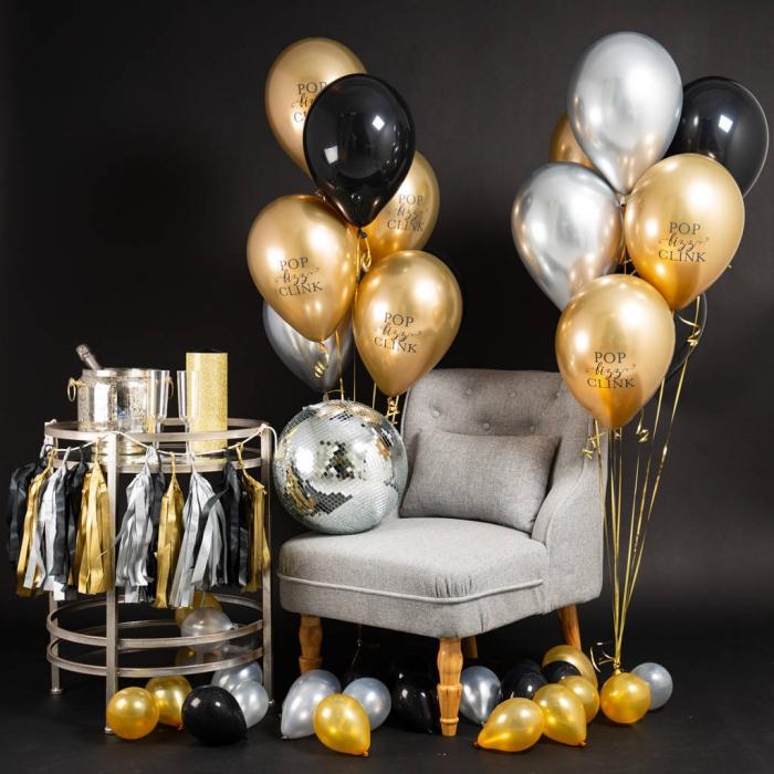 idée de deco anniversaire noir et or stylée, coin photobooth avec fauteuil gris et table métal à déco ballons hélium