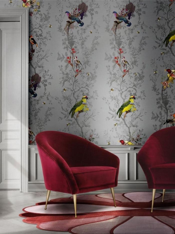 deco tendance 2020 dans un salon aux murs en papier peint gris à motifs oiseaux colorés aménagé avec meubles en velours rouge