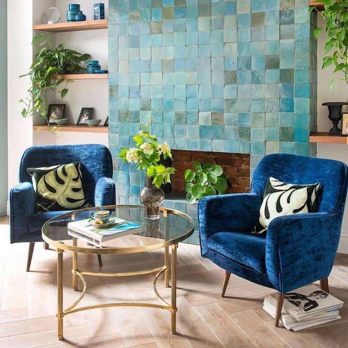 fauteuils bleu marine dans un salon avec cheminée bleu clair carrelage, étagères de bois ouvertes, accents bleu paon, table verre et laiton
