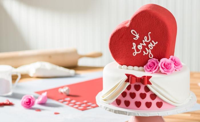 modèle de gâteau romantique au fondant blanc décoré avec figurines en fondant rouge sous forme de petits coeurs