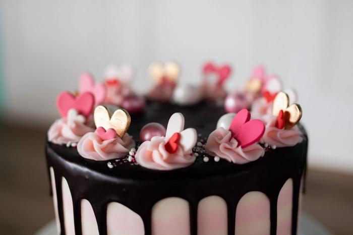 exemple comment décorer un gâteau romantique au chocolat noir avec coeurs comestibles et mini fleurs en crème rose