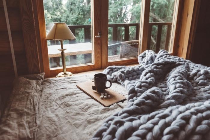 idée déco chambre adulte de style hygge, aménagement petite chambre à coucher aux murs en bois avec grand lit cocooning