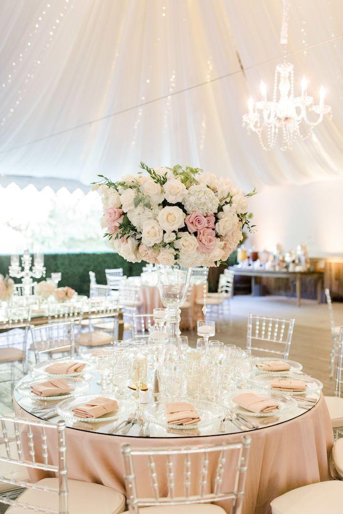 décoration mariage table en nappe et serviettes rose pâle avec centre deco bouquet de fleurs enorme, ciel drapé, chaises transparentes