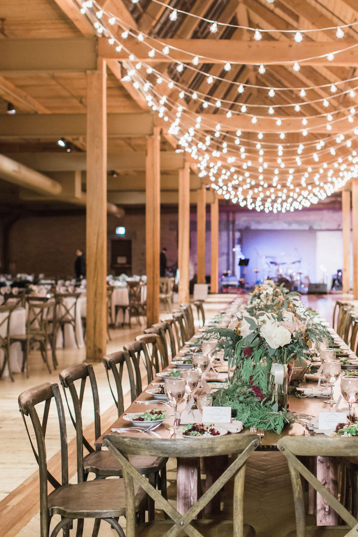 chaises et table bois brut décorées de centre de table florale en végétation et fleurs, plafond décoré de guirlande lumineuse
