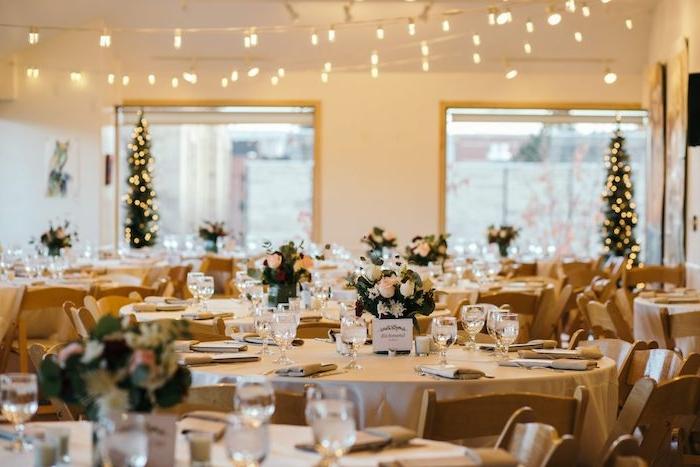 nappe beige et centre de table en roses, dco de petits sapins aux lumieres guirlande lumineuse, theme mariage noel