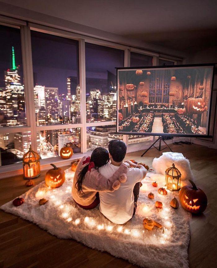 Couple amoureuse célébrant la fete d'amour avec citrouilles et guirlandes lumineuses regardant les films de Harry Potter, la magie est vive