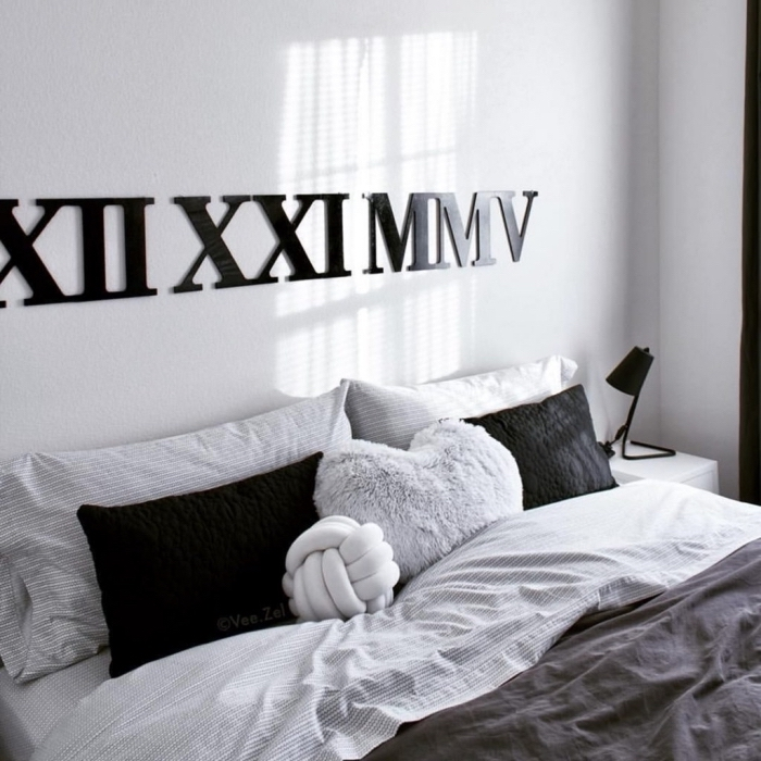 exemple de chambre gris et blanc décoré de style hygge avec grand lit couvert de coussins décoratifs en noir et gris