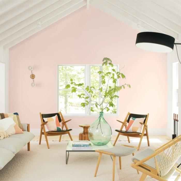 comment aménager une salle de séjour moderne aux murs roses avec meubles en bois et coussins multicolore
