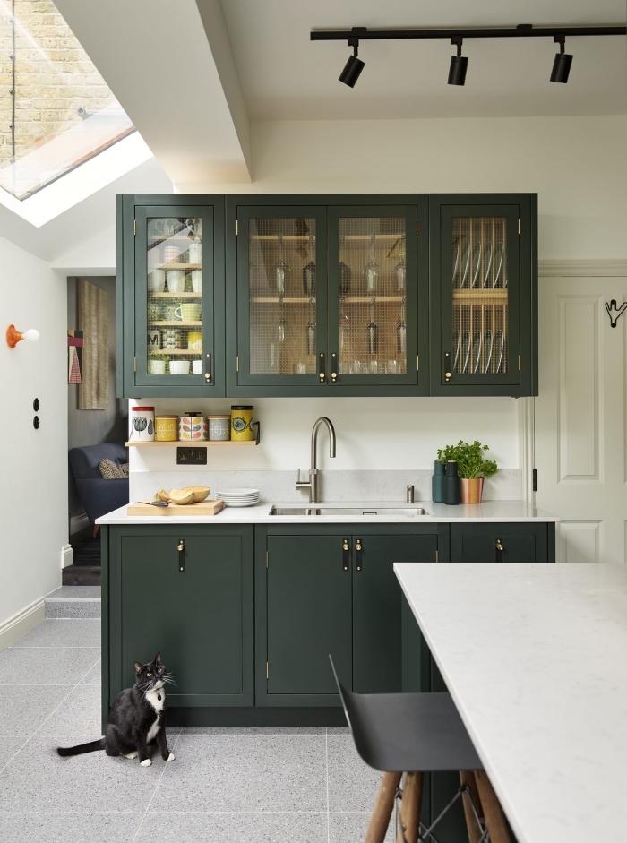 modèle de petite cuisine blanche avec crédence en carrelage gris clair et meubles de nuance vert de gris à poignées noires