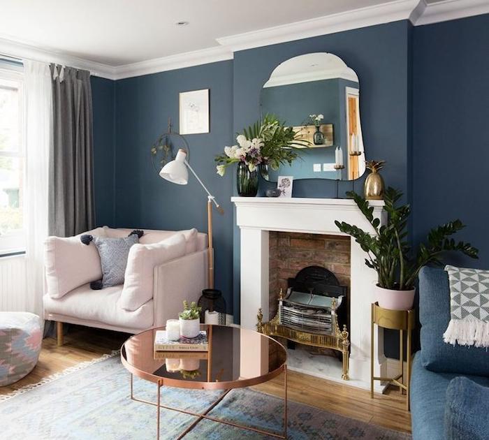 cheminée décorative de salon aux murs bleus avec miroir, fauteuil rose clair, table basse en cuivre, plantes decoratives