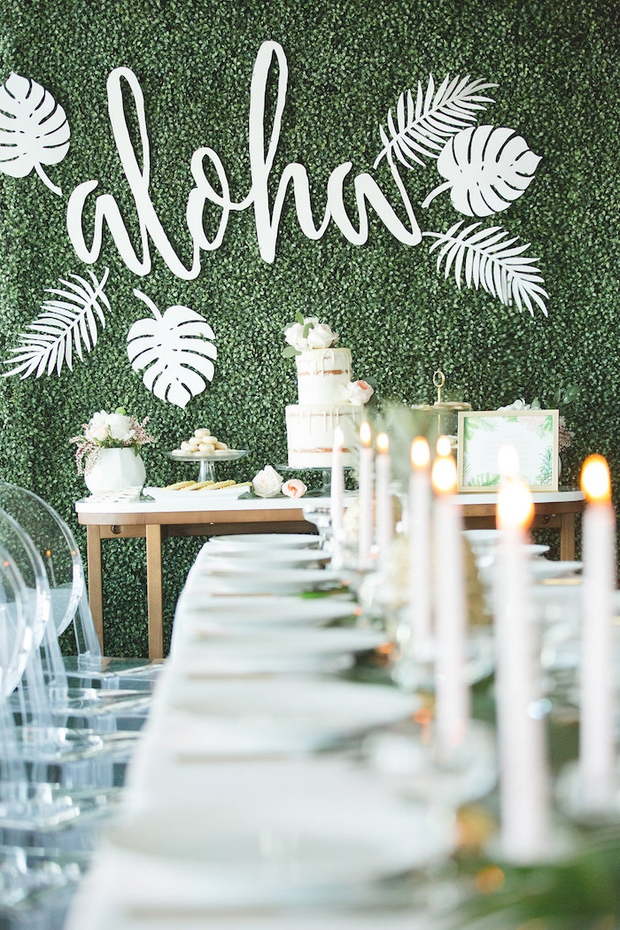 i;dee thème mariage hawaii avec mur décorée de végétation verte avec mot aloha, candy bar mariage blanc, centre de table mariage feuillages et bougies blanches