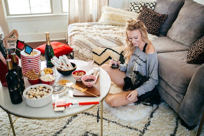 canapé gris d angle, tapis scandinave, table avec pop corn et autres petites friandises pour soirée cinéma maison pour anniversaire