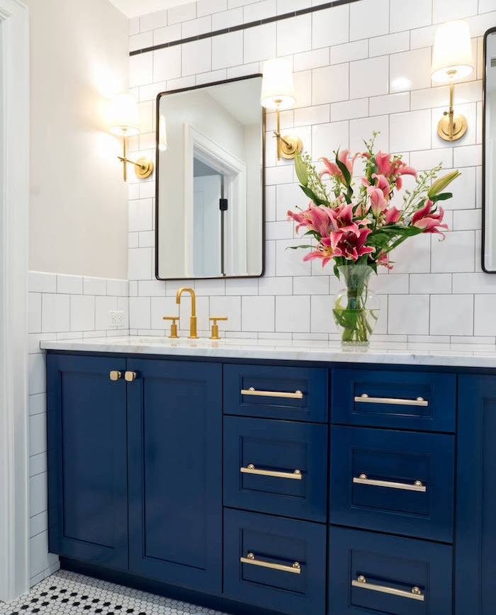 meuble bas salle de bain couleur bleu nuit dans une salle de bain blanc et bleu avec carrelage blanc, bouquet de fleurs et accents laiton